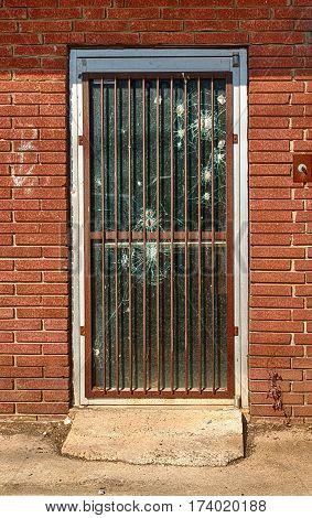 A bullet-ridden security door on an abandoned building in a high-crime area.