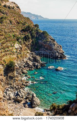 Beautiful lagoon with turqoise sea and rock ribbed shore and mountains covered with banana plantations shot on sunny day portrait layout