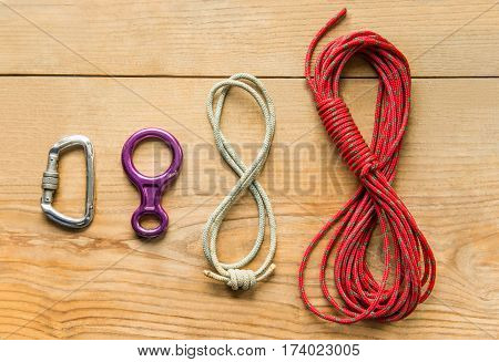 climbing equipment: rope, eight, carbine on wooden background, top view