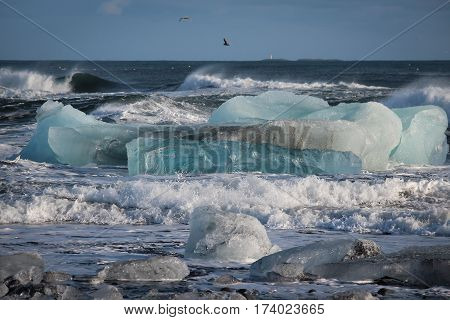 Beautiful blue glacial ice in sea, with breaking waves and surf on the beach near Jokulsarlon Lagoon, Iceland