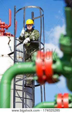 Oil and gas worker inside large petrochemical oil refinery