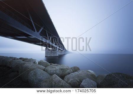 Long steel bridge over calm blue water
