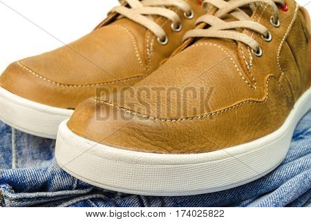 close-up view of tan color leather sneakers on jeans pant