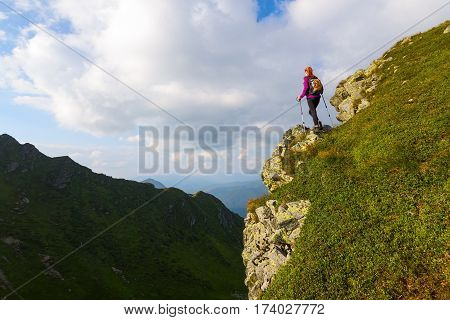 Sporty girl with back sack is standing at the edge of the precipice and watching on the endless vast of mountains landscape in the sunny day.