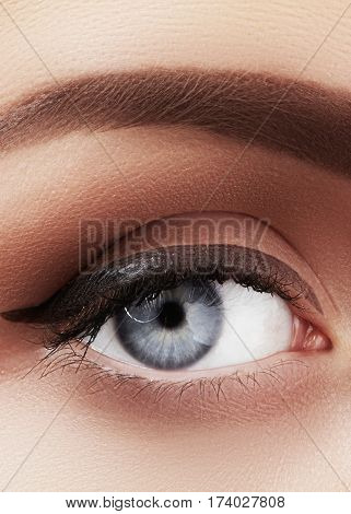 Close-up macro of beautiful female eye with perfect shape eyebrows. Clean skin fashion naturel make-up. Good vision.