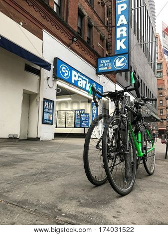 New York February 28 2017: Two bicycles are chained to a pole near a parking garage on Upper West Side.