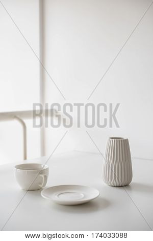 Clear white still-life, ceramic cup and vase on a table in light room interior. Modern minimalist decor.