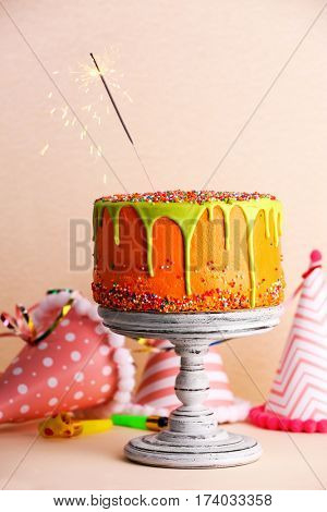 Cake with sparkler on color background