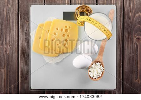 Kitchen scales with different dairy products on wooden background