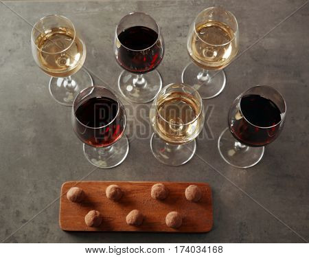 Delicious chocolate truffles and wine on grey background