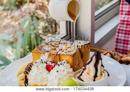 Hand pouring honey on Honey toast in restuarant.