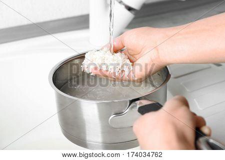 Woman rinsing rice in saucepan under running water