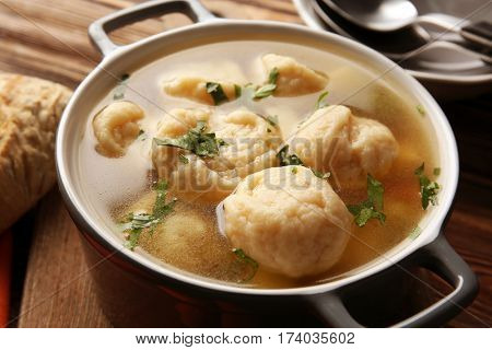 Ceramic pan with delicious chicken and dumplings on wooden cutting board