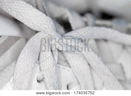 white shoelace knot on white gym shoes
