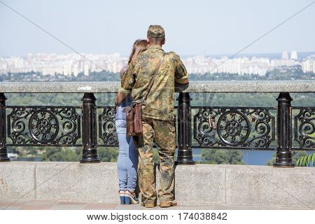 KIEV UKRAINE - AUGUST 8 2015: Ukrainian soldier on leave from the Eastern Ukraine conflict observing Kiev panorama with his girlfriend