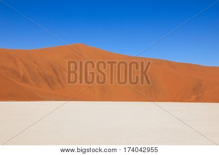 Tricolored graphical landscape with a huge red dune, white salt and clay pan and blue sky. The scenic Sossusvlei and Deadvlei, Namib, Namibia.
