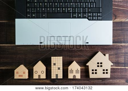Top View Of Office Stuff With Laptop And Wooden House Toy On Wooden Table.concept Workplace.real Est