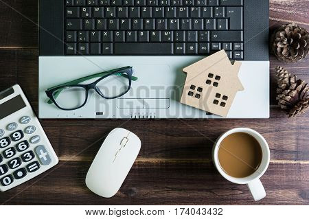 Top view of office stuff with laptop wireless mouse calculator coffee cup and wooden house toy on wooden table.Concept workplace.Real estate concept New house concept Finance loan business concept