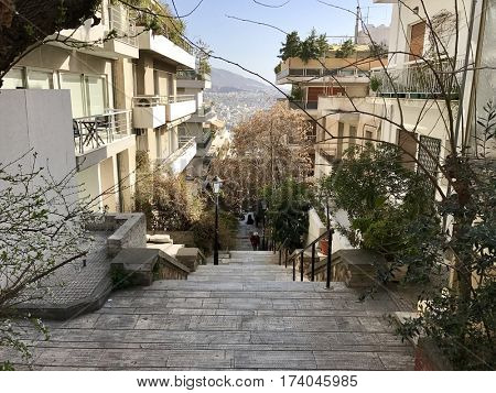 ATHENS - FEBRUARY 28, 2017: Pedestrian steps down the hill between city blocks at the foot of Mount Lycabettus in Athens, Greece.