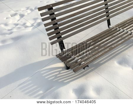 Winter Background Urban Scene park bench in sparkling winter snow after snowstorm conceptual weather image