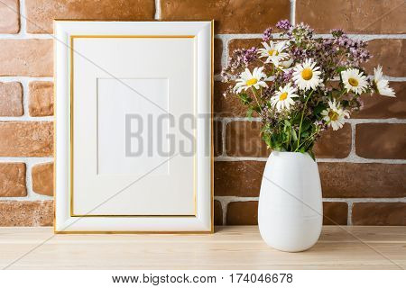 Gold decorated frame mockup with wildflowers bouquet in styled vase near exposed brick wall. Empty frame mock up for presentation design. Template framing for modern art.