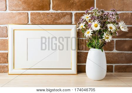 Gold decorated landscape frame mockup with wildflowers bouquet in styled vase near exposed brick wall. Empty frame mock up for presentation design. Template framing for modern art.