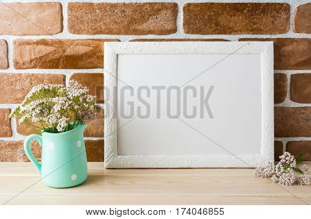 White landscape frame mockup with wild creamy pink flowers in mint pitcher near exposed brick wall. Empty frame mock up for presentation design. Template framing for modern art.