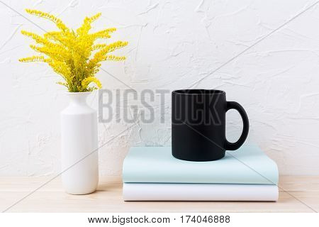 Black coffee mug mockup with ornamental golden grass and books. Empty mug mock up for brand promotion.