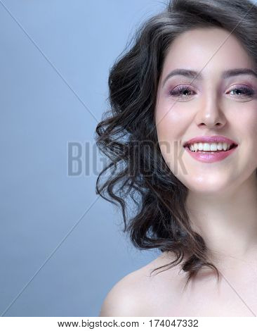Beauty Spa Woman with Perfect skin Portrait. Beautiful Brunette curly Hair. Young Caucasian with Fresh looking Skin. Beauty Woman Face. Blue background. Studio shot. Happy Cheerful Toothy Smiling