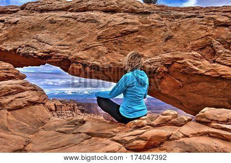 Woman hipster meditating at cliff by Mesa Arch. Canyonlands National Park. La SAl Mountains. Moab. Utah. United States.