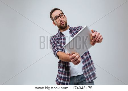 Bearded man in eyeglasses which playing on tablet computer. Isolated gray background