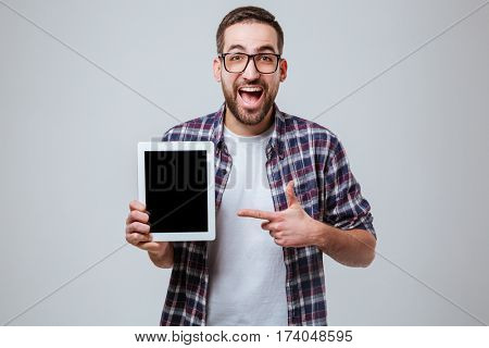 Happy Bearded man in eyeglasses with open mouth which showing blank tablet computer screen and pointing at him