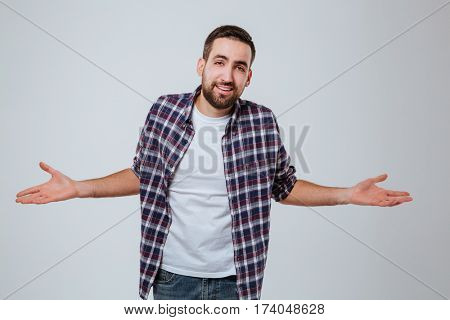 Uncomprehending Bearded man in shirt with hand to the sides which looking at camera. Isolated gray background