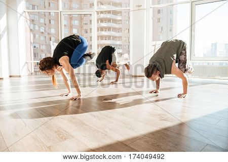 Group of people balancing on hands and practicing yoga in studio