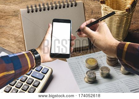 Hand in hipster shirt holding blank smartphone with gold coin calculator and banking account in background for finance planning concept