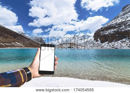 Hand in hipster shirt holding blank smartphone with green lake and snow mountain background for mocup your product display.