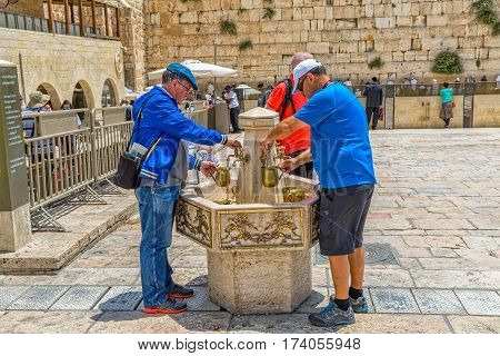 JERUSALEM, ISRAEL - MAY 23, 2016: Ritual of hand washing at the Western Wall, Wailing Wall or Kotel witch is located in the Old City at the foot of the western side of the Temple Mount.