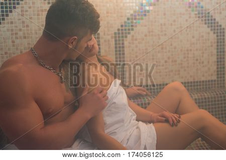 Gorgeous longhaired young blonde wrapped in white towel and her sexy athletic lover tenderly embracing her in hamam