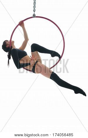 Young gymnast in black sexy top and stockings perfoming exercises on aerial hoop in studio