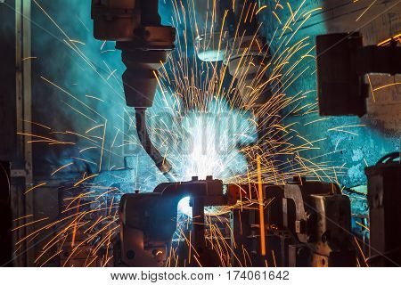Motion Welding robots in a car factory with sparks, manufacturing, industry