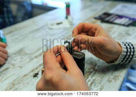 Male Hands Fill Cotton Wool For The E-cigarette. After-sales Service Of The Electronic Cigarette. En