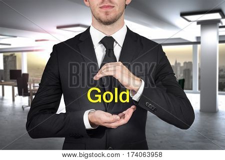 businessman in black suit protecting word gold with hands office