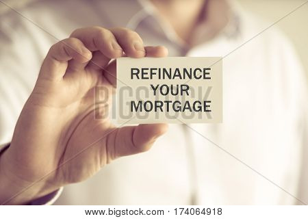 Businessman Holding Refinance Your Mortgage Message Card