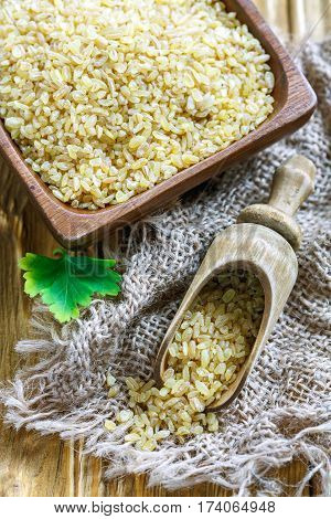 Wooden Bowl And Scoop With Bulgur Wheat.