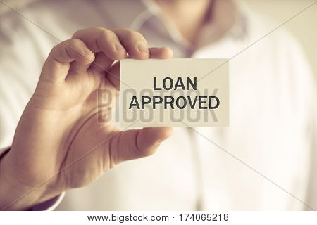 Businessman Holding Loan Approved Message Card
