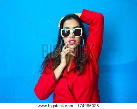 Fashion sexy fierce model in white sunglasses, beautiful young woman with hand in her head and in her face with long brunette hair and red clothes in bright vibrant blue background
