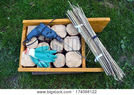 Insect hotel material and tools in spring garden on grass