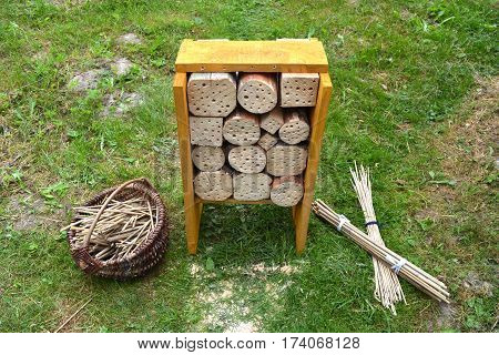 Insect hotel construction and reeds in basket in spring garden on grass