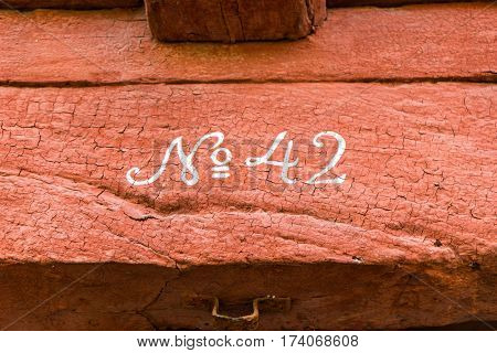 Number 42. wooden beam with cracked red paint and white Gothic numerals written No 42