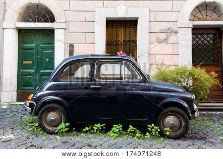 ROME Italy - November 29 2015: Old car Fiat 500 abandoned in a street of the old town.